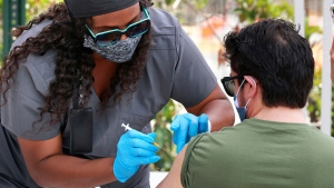 In this June 17, 2021, file photo, an Orange County resident receives the COVID-19 vaccine at the Florida Division of Emergency Management mobile vaccination site at Camping World Stadium in Orlando, Fla. (Joe Burbank/Orlando Sentinel via AP, File)