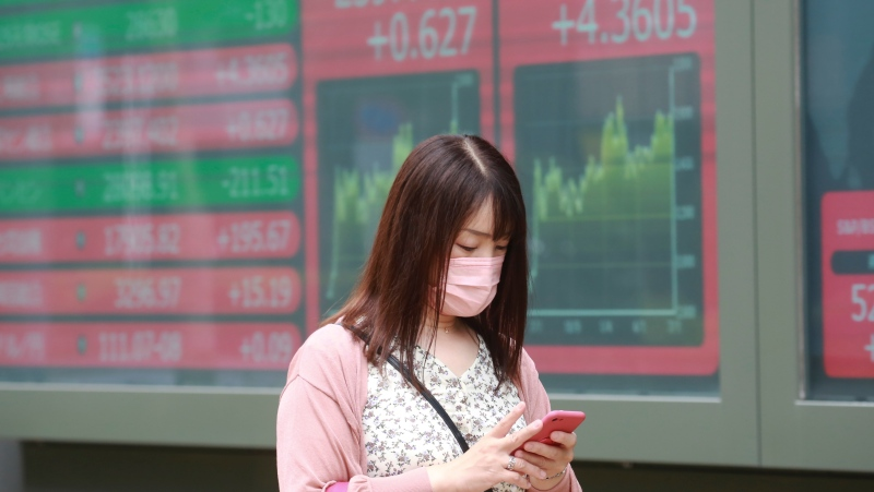 A woman walks by an electronic stock board of a securities firm in Tokyo, Monday, July 5, 2021. Shares were mixed Monday in Asia in quiet trading, with U.S. markets set to be closed for the Independence Day holiday. (AP Photo/Koji Sasahara)