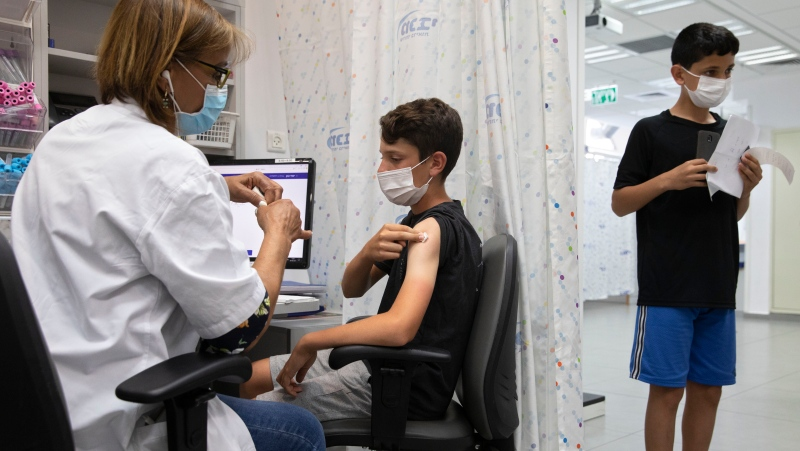 An Israeli youth receives a Pfizer-BioNTech COVID-19 vaccine in the central Israeli city of Rishon LeZion, Sunday, June 6, 2021. Israel started vaccinating children from 12 to 15 on Sunday. (AP Photo/Sebastian Scheiner)