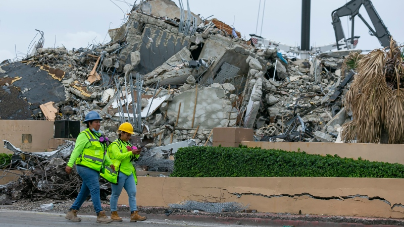 A workers make her way past the rubble and debris of the Champlain Towers South condo in Surfside, Fla. on Tuesday, July 6, 2021. (Matias J. Ocner/Miami Herald via AP)
