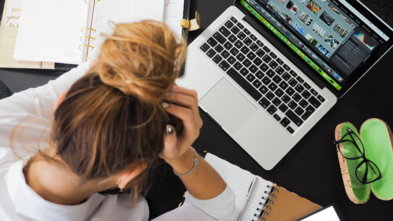 A woman puts her head in her hands at her desk in this stock image. (Pexels)