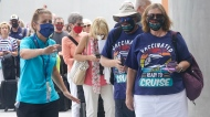 Orchid Klaric, left, assists Brenda and Kurt Duncan of Denver, with checking into their cruise, Saturday, June 26, 2021, in Fort Lauderdale, Fla. (AP Photo/Marta Lavandier)