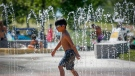 A young boy runs through a fountain at a splash park trying to beat the heat in Calgary, Alta., Wednesday, June 30, 2021. (THE CANADIAN PRESS / Jeff McIntosh)