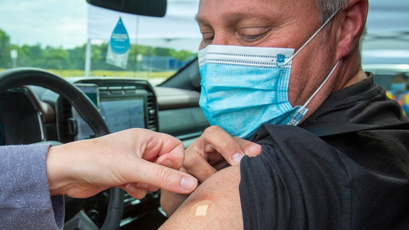 A person looks at their bandage after receiving his COVID-19 vaccine during a drive-thru clinic at Richardson stadium in Kingston, Ont., on Friday, Jul. 2, 2021. THE CANADIAN PRESS/Lars Hagberg
