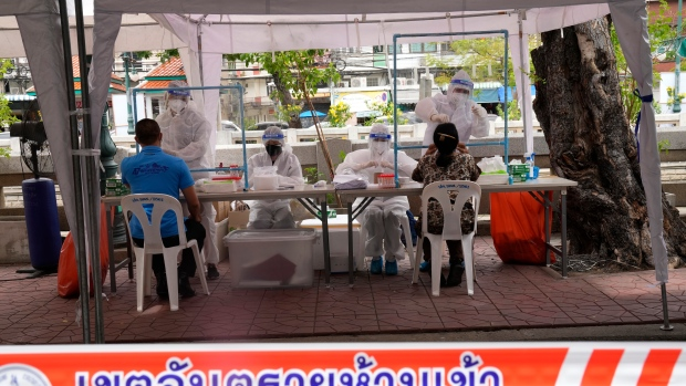 Health workers collect nasal swabs from local residents for coronavirus testing in Bangkok, Thailand, Thursday, July 8, 2021. (AP Photo/Sakchai Lalit)