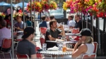 A patron drinks a beverage at a patio in the Byward Market in Ottawa, as patios open in Ontario's first phase of re-opening amidst the third wave of the COVID-19 pandemic, on Saturday, June 12, 2021. THE CANADIAN PRESS/Justin Tang