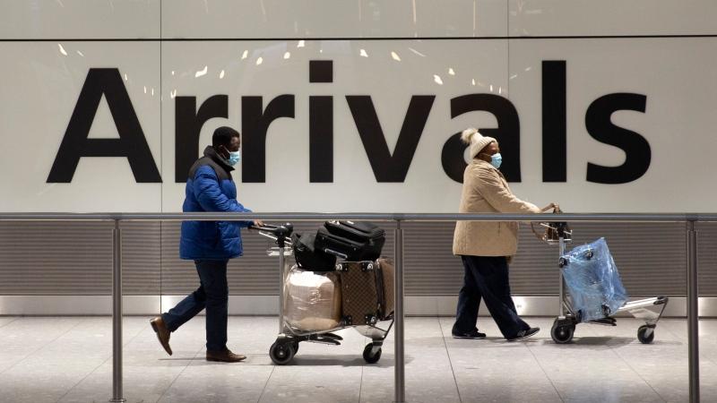 Arriving passengers walk past a sign in the arrivals area at Heathrow Airport in London, Tuesday, Jan. 26, 2021. (AP Photo/Matt Dunham)