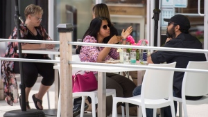 People sit on a patio placed on street parking spaces outside a restaurant in Ottawa on the first day of Ontario's first phase of re-opening amidst the third wave of the COVID-19 pandemic, on Friday, June 11, 2021. THE CANADIAN PRESS/Justin Tang