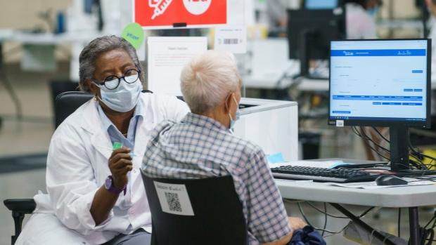 Regine Laurent, former president of the Fédération interprofessionnelle de la santé du Québec (FlQ), vaccinates a man at a COVID-19 vaccination clinic in Montreal, on Monday, June 21, 2021. THE CANADIAN PRESS/Paul Chiasson