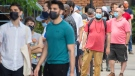 People wear face masks as they line up for a COVID-19 vaccine shot at an outdoor clinic in Montreal, Saturday, July 10 2021, as the COVID-19 pandemic continues in Canada and around the world. THE CANADIAN PRESS/Graham Hughe
