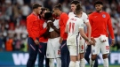 England players comfort teammate Bukayo Saka after he failed to score a penalty during a penalty shootout after extra time during of the Euro 2020 soccer championship final match between England and Italy at Wembley stadium in London, Sunday, July 11, 2021. (Carl Recine/Pool Photo via AP)