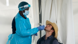 A visitor to Nashville North has a rapid COVID test at the Calgary Stampede in Calgary, Friday, July 9, 2021. THE CANADIAN PRESS/Jeff McIntosh