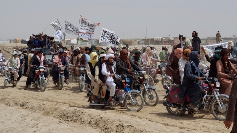 Supporters of the Taliban carry the Taliban's signature white flags in the Afghan-Pakistan border town of Chaman, Pakistan, Wednesday, July 14, 2021. (AP Photo/Tariq Achkzai)
