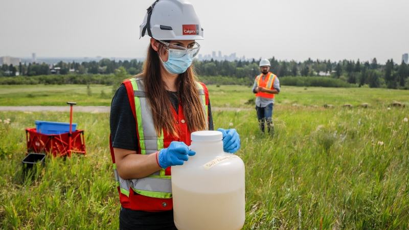 City of Calgary industrial technician Dierdre Jenkins holds a jug of wastewater at a collection site as University of Calgary researchers check monitoring equipment for traces of COVID-19 in the wastewater system in Calgary, Alta., Wednesday, July 14, 2021.THE CANADIAN PRESS/Jeff McIntosh