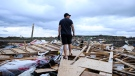 A resident surveys the damage left after a tornado touched down in his neighbourhood, in Barrie, Ont., on Thursday, July 15, 2021. (THE CANADIAN PRESS/Christopher Katsarov )
