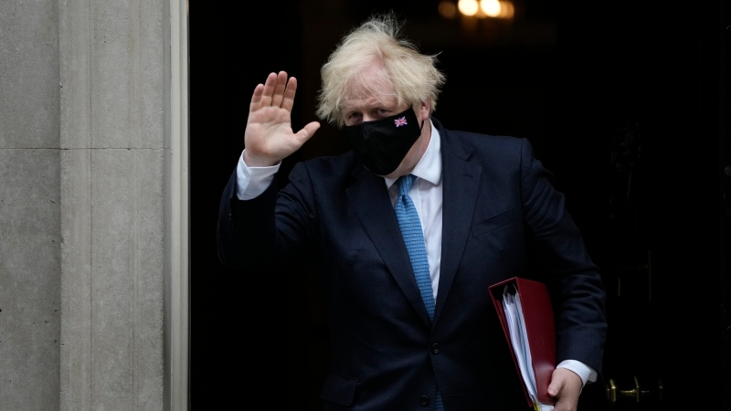 British Prime Minister Boris Johnson waves at the media as he leaves 10 Downing Street to attend the weekly Prime Minister's Questions at the Houses of Parliament, in London, Wednesday, July 14, 2021. (AP Photo/Matt Dunham)