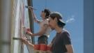 Derek and Kyle Simmers restoring a mural in Bashaw, Alta. (Courtesy: Tim Ursuliak)