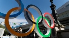 A woman reads on her cellphone as she walks by the Olympic rings installed by the Nippon Bashi bridge in Tokyo on Thursday, July 15, 2021. (AP Photo/Hiro Komae)