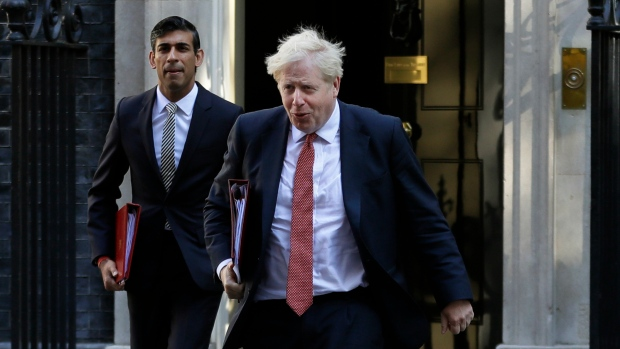 In this Tuesday, Sept. 1, 2020 file photo, Britain's Prime Minister Boris Johnson and Chancellor Rishi Sunak, left, leave Downing Street to attend a cabinet meeting in London. (AP Photo/Kirsty Wigglesworth, File)