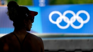 Brandie Wilkerson, from Canada, waits in the shade before women's beach volleyball practice at the 2020 Summer Olympics, Monday, July 19, 2021, in Tokyo. (AP Photo/Charlie Riedel)
