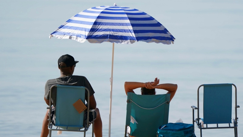 People relax under a sun shade on the beach during a hot morning at Bournemouth, southern England, Tuesday July 20, 2021. (Andrew Matthews/PA via AP)