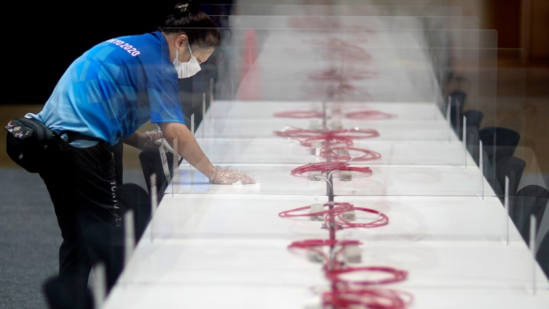 A worker wipes down a table in the main press center as part of COVID-19 countermeasures at the 2020 Summer Olympics, Tuesday, July 20, 2021, in Tokyo. (AP Photo/David Goldman)