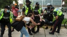 An encampment supporter is detained by the police as city officials work to clear Alexandra Park encampment in Toronto on Tuesday, July 20, 2021. THE CANADIAN PRESS/Chris Young