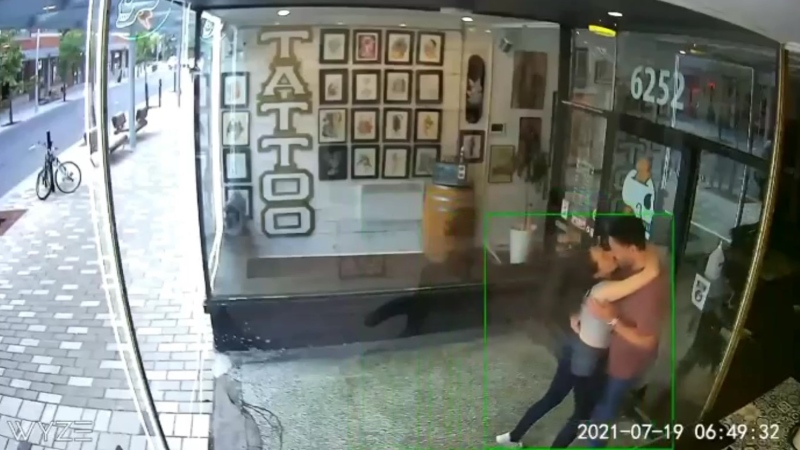 A still from a surveillance video shared on Facebook shows a couple making out just before crashing through a glass door of a Montreal barbershop. (Source: Savvy Barbershop/Facebook)