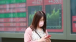 A woman walks by an electronic stock board of a securities firm in Tokyo, Monday, July 5, 2021. (AP Photo/Koji Sasahara)