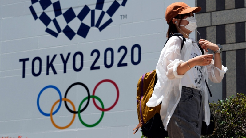 In this Tuesday, July 20, 2021, file photo, a woman wearing a protective mask walks in front of a Tokyo 2020 Summer Olympics display at the Tokyo Metropolitan government in Tokyo. (AP Photo/Kiichiro Sato, File)