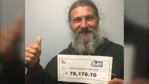 Anastasios Panagopoulos, 47, of Tiny Township holds his big cheque after winning Lotto 6/49. (OLG)