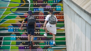 Two people make their way up a painted staircase in Ottawa on Monday, July 19, 2021. (Sean Kilpatrick/THE CANADIAN PRESS)