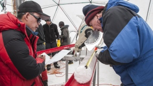 Yao Tandong, left, and Lonnie Thompson, right, process an ice core drilled from the Guliya Ice Cap in the Tibetan Plateau in 2015. The ice held viruses nearly 15,000 years old, a new study has found. (Ohio State University)
