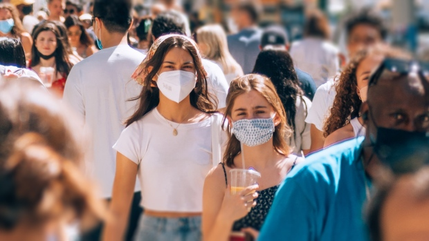 People walk down a busy street wearing masks during the COVID-19 pandemic. (Photo by Yoav Aziz on Unsplash)