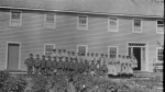 Lac La Ronge Indian Residential School students stand outside of the school by a garden in this undated photo. (Library and Archives Canada)
