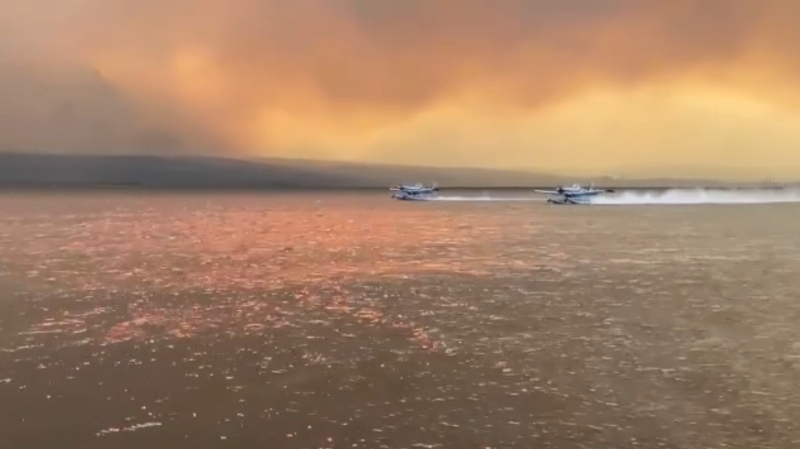 Firefighting planes refill their pontoons before returning to fight a wildfire burning near Osoyoos, B.C.