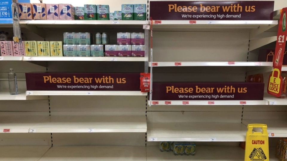 Empty shelves and signs in a supermarket