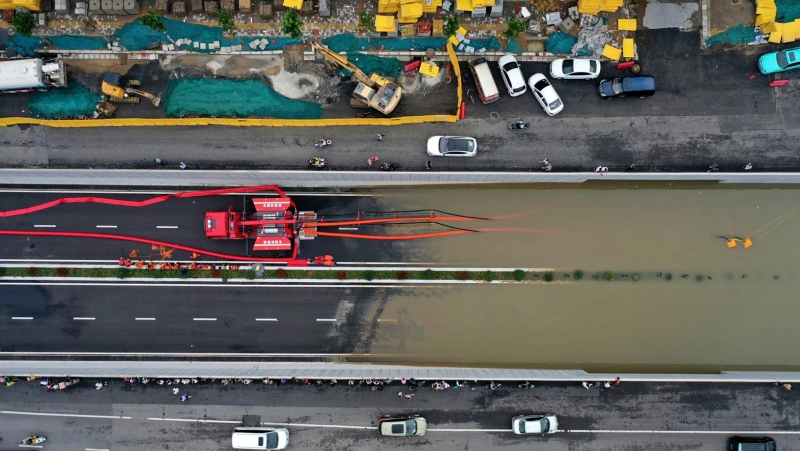 In this aerial photo released by Xinhua News Agency, firefighters pump rainwater from a road underpass in Zhengzhou in central China's Henan province on Wednesday, July 21, 2021. (Ma Xiaoran/Xinhua via AP)