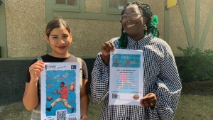 """Yulissa Campos and K.P hold up posters advertising """"The Newcomer."""""""