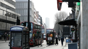 In this file photo, a coronavirus information sign is displayed by a bus stop with a Union flag above in London, Friday, Jan. 15, 2021, during England's third national lockdown since the coronavirus outbreak began. (AP Photo/Matt Dunham)