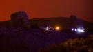The sky glows orange as the Tremont Creek wildfire burns on a mountain in the distance behind homes in Ashcroft, B.C., on Thursday, July 15, 2021. THE CANADIAN PRESS/Darryl Dyck