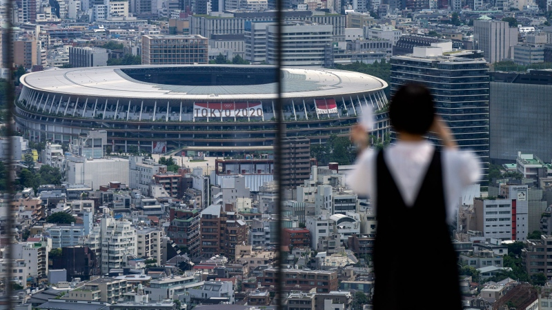 A person wearing a protective mask takes a picture from an observation deck as National Stadium, where the opening ceremony of the Tokyo 2020 Olympics will be held in less than two weeks is seen in the background Saturday, July 10, 2021, in Tokyo. (AP Photo/Kiichiro Sato)