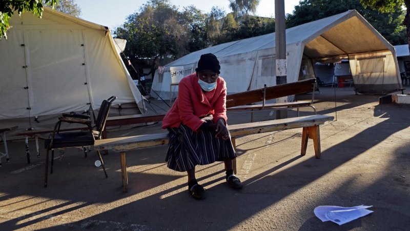 A woman sits on a bench while pondering her next move after COVID-19 vaccines ran out at a government hospital in Harare, Zimbabwe, on Saturday, July, 10, 2021. (AP Photo/Tsvangirayi Mukwazhi)