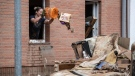 A woman throws rubbish from the window of her home onto a pile of discarded goods in the district of Blessem, in Ergfstadt, Germany, Thursday July 22, 2021. (Marius Becker/dpa via AP)