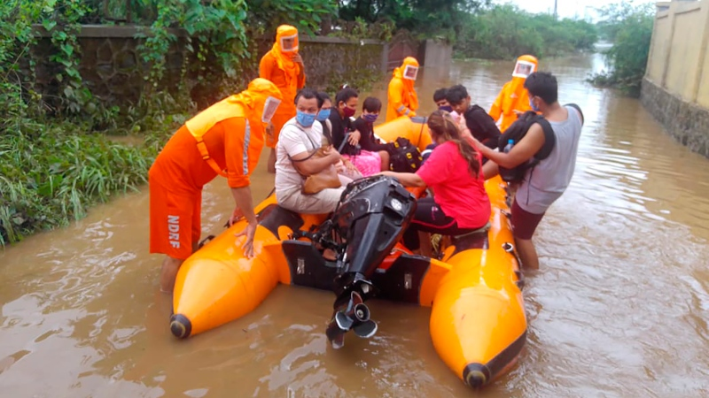 This photograph provided by India's National Disaster Response Force (NDRF) shows NDRF personnel rescuing people stranded in floodwaters in Bhiwandi, in the western Indian state of Maharashtra, Thursday, July 22, 2021. (National Disaster Response Force via AP)