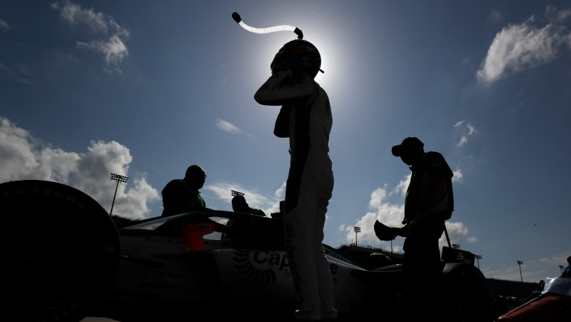 A driver puts on his helmet on during qualifying for an IndyCar Series auto race in this file photo from July 17, 2020 taken in Iowa. (AP Photo/Charlie Neibergall)