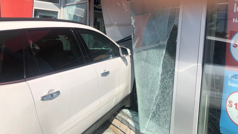 A white Chevy Traverse smashes through a window exterior wall at a Shoppers Drug Mart on Broadway in Orangeville, Ont. on Fri. July 23, 2021. (OPP/Twitter)