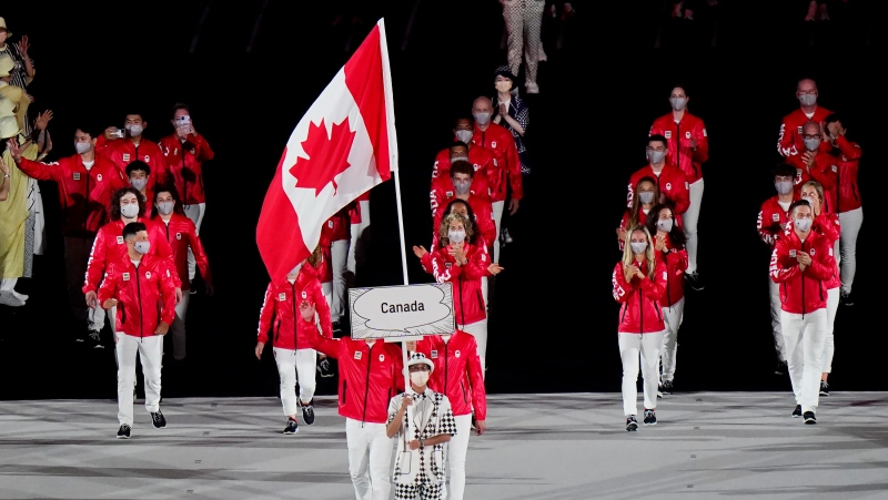 Team Canada flag-bearers Miranda Ayim and Nathan Hirayama carry the Canadian flag at the opening ceremonies during the Tokyo Olympics in Tokyo, Japan on Friday, July 23, 2021. THE CANADIAN PRESS/Adrian Wyld
