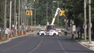 Police block traffic as crews repair a downed hydro pole in London, Ont. on Friday, July 23, 2021. (Jim Knight / CTV News)