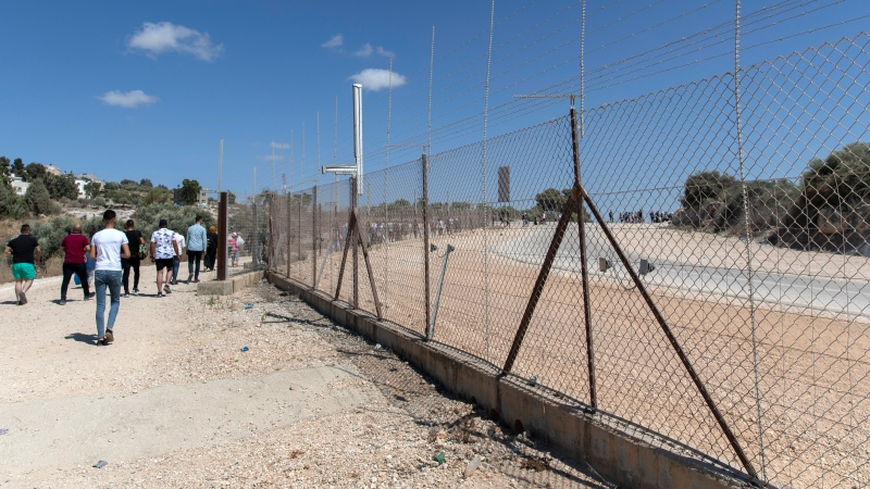 Palestinians cross into Israel through a damaged section in the Israeli separation fence, aiming for a day on the beach as they celebrate the second day of Eid al-Adha, in the West Bank village of Faroun, near Tulkarm, Wednesday, July. 21, 2021. (AP Photo/Nasser Nasser)